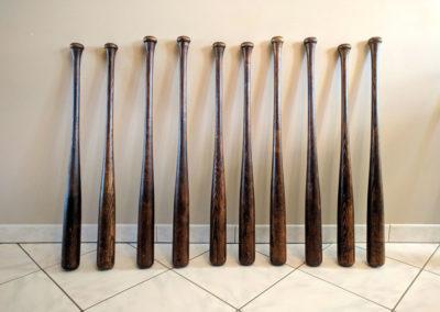 10 battes de baseball vintage présentées l'une à côté de l'autre.