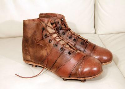 Ancienne paire de chaussure crampons présentée en déco sur un canapé