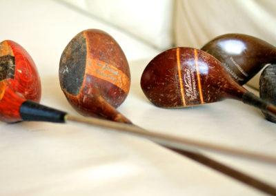 Vue macro de la tête d'une ancien club de golf bois posé avec d'autres clubs