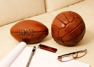 Le ballon de rugby pour bébé posé à côté d'un mini ballon de foot