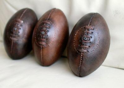 un mini ballon de rugby en cuir présenté avec ses 2 frères