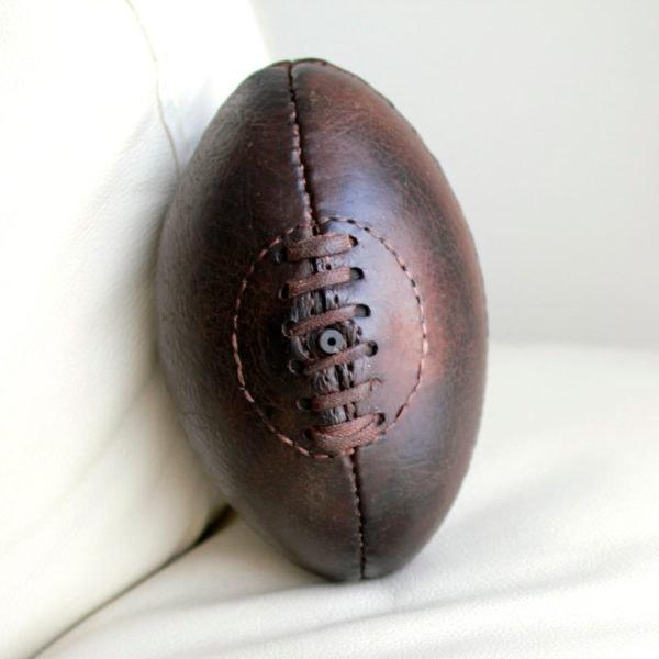 photo carrée d'un ballon accoudé à son canapé en cuir blanc à la lumière du jour