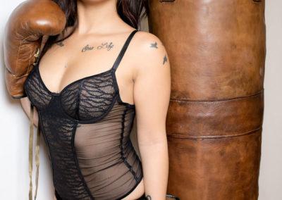 Une femme en lingerie avec des gants de boxe et un sac de frappe en cuir