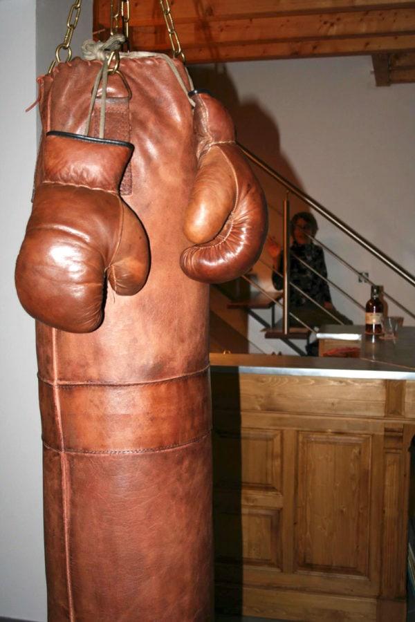 Sac de frappe en cuir accroché sur une poutre en bois
