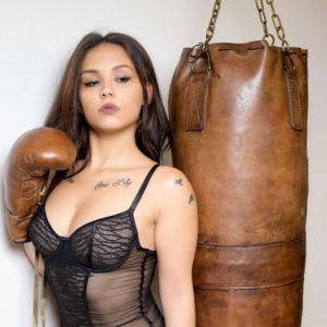Une belle asiatique en lingerie avec ls gants de boxe en cuir et le sac de frappe en cuir vintage