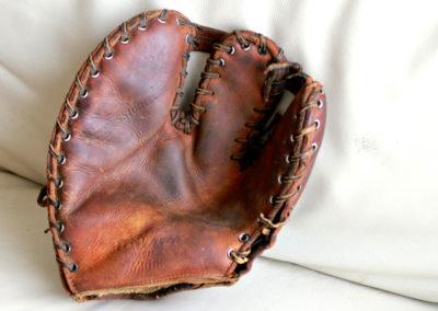 Gant de baseball avec du vieux cuir posé sur un canapé