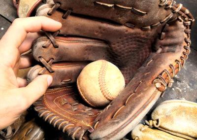 Un gant de baseball vintage avec sa balle posé sur un établi