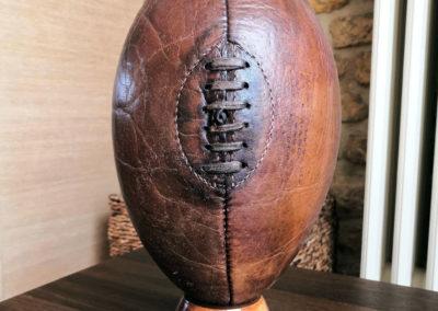 Un ballon de rugby posé sur un tee en bois